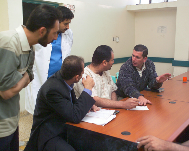 Two representatives of the Iraqi Ministry of Health (seated left and right) speak with Iraqi civilian workers at the allujah General Hospital, in the city of allujah, Al Anbar Province, Iraq, on Nov. 24, 2004, to get a clearer assessment of the condition of the hospital and what needs to be done to improve it. U.S. Marine Corps 4th Civil Affairs Group Marines and Iraqi Ministry of Health representatives are inspecting various medical facilities to estimate what repairs are necessary to get the them back to full functionality. This assessment is being done at the conclusion of the week-long battle by Multinational orces against insurgents in the city of allujah, during Operation Iraqi...