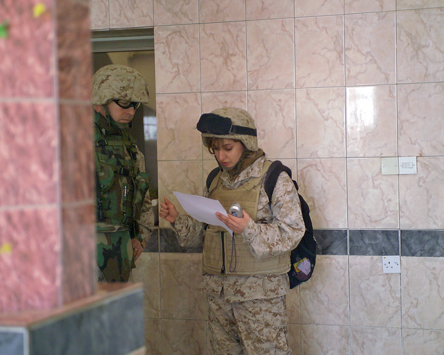 """U.S. Marine Corps MAJ. Francis Piccoil (left), Deputy Public Affairs Officer, I Marine Expeditionary Force, asks""""Rose""""(right), an Iraqi interpreter, to translate a paper for him while they are inside the Dr. Talib Al-Janabi Hospital, in the city of Fallujah, Al Anbar Province, Iraq, on Dec. 2, 2004. This hospital is one stop for the foreign media as they tour various sites in Fallujah to see the reconstruction efforts going on after the November battle by Multinational Forces against insurgents in the city of Fallujah, during Operation Iraqi Freedom. (U.S. Marine Corps photo by CPL. Theresa M. Medina) (Released)"""