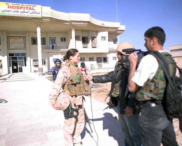 U.S. Marine Corps MAJ. M. Naomi Hawkins (left), Public Affairs Officer, 4th Civil Affairs Group, is interviewed by an Arab television news crew (right) in front of the Dr. Talib Al-Janabi Hospital, in the city of Fallujah, Al Anbar Province, Iraq, on Dec. 2, 2004. The foreign media is on a tour of various sites in Fallujah to see the reconstruction efforts going on after the November battle by Multinational Forces against insurgents in the city of Fallujah, during Operation Iraqi Freedom. (U.S. Marine Corps photo by CPL. Theresa M. Medina) (Released)