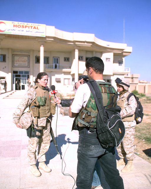 U.S. Marine Corps MAJ. M. Naomi Hawkins (left), Public Affairs Officer, 4th Civil Affairs Group, is interviewed by an Arab television news crew (center), as 'Rose' (right), an Iraqi interpreter, listens, in front of the Dr. Talib Al-Janabi Hospital, in the city of Fallujah, Al Anbar Province, Iraq, on Dec. 2, 2004. The foreign media is on a tour of various sites in Fallujah to see the reconstruction efforts going on after the November battle by Multinational Forces against insurgents in the city of Fallujah, during Operation Iraqi Freedom. (U.S. Marine Corps photo by CPL. Theresa M. Medina) (Released)