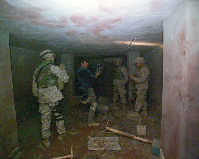 U.S. Marine Corps Marines and foreign news reporters gather information inside a bloody basement in an unmarked Islamic Resistance Center building, located in the city of Fallujah, Al Anbar Province, Iraq, on Dec. 2, 2004. This basement may have served as a torture chamber and is being shown to the foreign media as part of their tour of various sites within the city of Fallujah to see the reconstruction efforts going on after the November battle between Multinational Forces and insurgents in the city of Fallujah, during Operation Iraqi Freedom. (U.S. Marine Corps photo by CPL. Theresa M. Medina) (Released) (SUBSTANDARD)