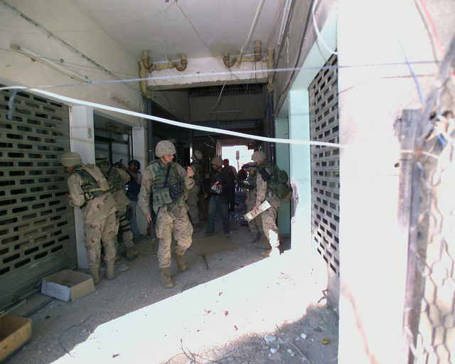 U.S. Marine Corps Marines and foreign news reporters gather information inside an unmarked Islamic Resistance Center building, located in the city of Fallujah, Al Anbar Province, Iraq, on Dec. 2, 2004. This insurgent facility is being shown to the foreign media as part of their tour of various sites within the city of Fallujah to see the reconstruction efforts going on after the November battle between Multinational Forces and insurgents in the city of Fallujah, during Operation Iraqi Freedom. (U.S. Marine Corps photo by CPL. Theresa M. Medina) (Released)