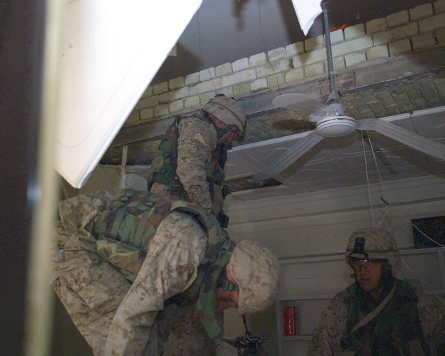 U.S. Marine Corps Marines climb down from the ceiling where they found weapons in what appears to be a weapons-making factory in the back of a computer store on the first floor of an unmarked Islamic Resistance Center building, located in the city of Fallujah, Al Anbar Province, Iraq, on Dec. 2, 2004. The Marines are clearing the building so that foreign news reporters may enter the building to gather information for their news stories. The foreign media is touring various sites in Fallujah to see the reconstruction efforts going on after the November battle between Multinational Forces and insurgents in the city of Fallujah, during Operation Iraqi Freedom. (U.S. Marine Corps photo by...