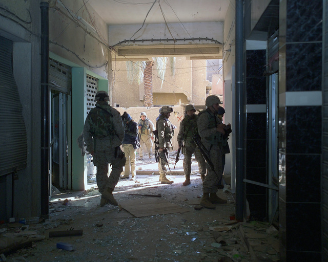 U.S. Marine Corps Marines remain watchful for insurgents while foreign reporters gather information for their news stories inside a bloody basement in an unmarked Islamic Resistance Center building, located in the city of Fallujah, Al Anbar Province, Iraq, on Dec. 2, 2004. This basement may have served as a torture chamber and is being shown to the foreign media as part of their tour of various sites within the city of Fallujah to see the reconstruction efforts going on after the November battle between Multinational Forces and insurgents in the city of Fallujah, during Operation Iraqi Freedom. (U.S. Marine Corps photo by CPL. Theresa M. Medina) (Released)