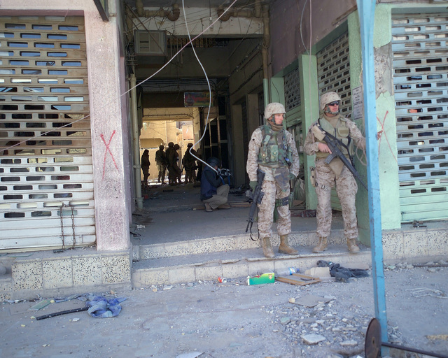 U.S. Marine Corps Marines stand guard as foreign news reporters gather information inside an unmarked Islamic Resistance Center building, located in the city of Fallujah, Al Anbar Province, Iraq, on Dec. 2, 2004. This insurgent facility is being shown to the foreign media as part of their tour of various sites within the city of Fallujah to see the reconstruction efforts going on after the November battle between Multinational Forces and insurgents in the city of Fallujah, during Operation Iraqi Freedom. (U.S. Marine Corps photo by CPL. Theresa M. Medina) (Released)