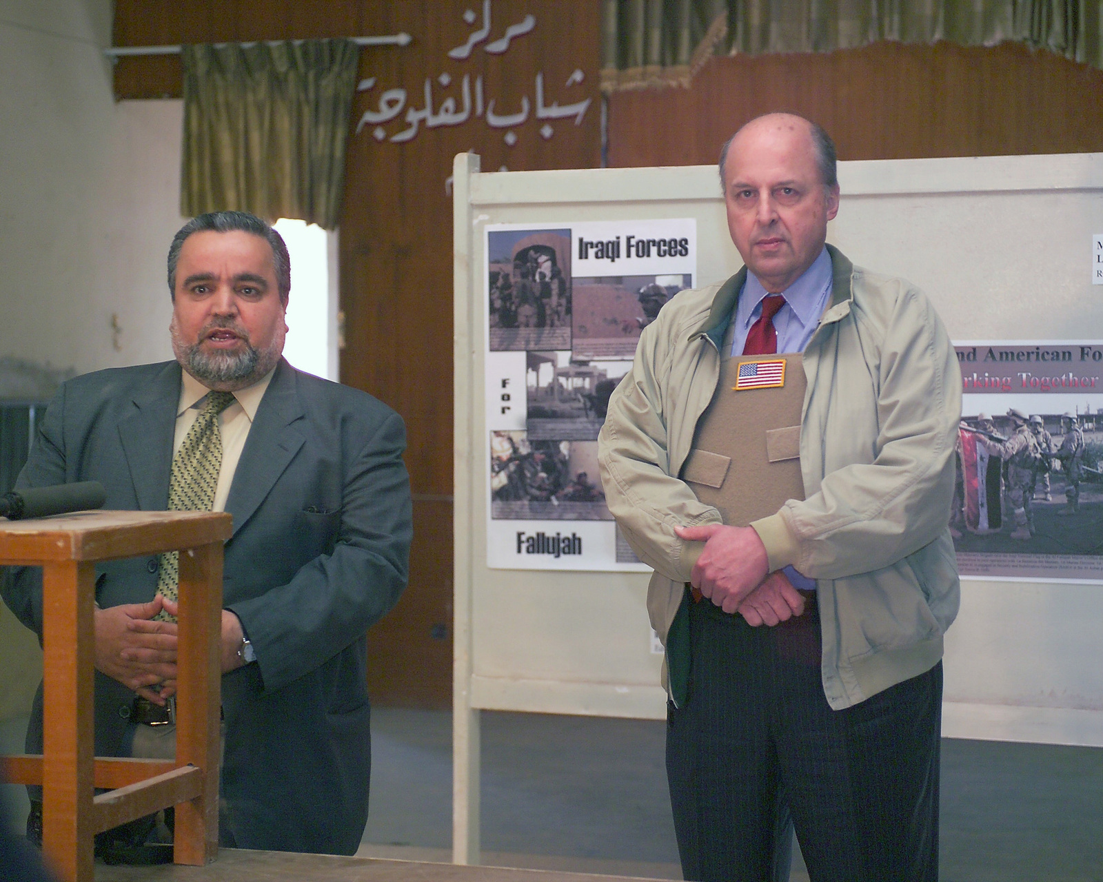The Honorable John D. Negroponte (right), U.S. Ambassador to Iraq, listens as the Honorable Dr. Hajim al-Hasani (left), Minister, Iraqi Ministry of Industry and Minerals (MIM), speaks at a press conference while visiting the U.S. e Corps 4th Civil Affairs Group Civil Military Operations Center, in the city of Fallujah, Al Anbar Province, Iraq, on Nov. 27, 2004. Dr. al-Hasani, Ambassador Negroponte, and the Honorable William B. Taylor, Jr., Director, Iraq Reconstruction Management Office, are touring the city of Fallujah to assess the damage at the end of the week-long battle by Multinational Forces against insurgents in the city of Fallujah, during Operation Iraqi Freedom. (U.S....