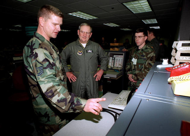 Medium shot, from the left, Noncomissioned Officer In Charge of the Maintenance Aircraft Coordination Center MASTER Sergeant Mark Clark, Air Force Deputy CHIEF of STAFF for Air and Space Operations Lieutenent General Marvin R. Esmond, and 319th Air Refueling Wing CHIEF of Command and Control Lieutenent Colonel Cliff Fitts, look at the Air Mobility Advanced Console System recently added to the Command Post at Grand Forks Air Force Base, ND. The General was present for a ribbon cutting and tour of the newly renovated facility on 26 January 2000