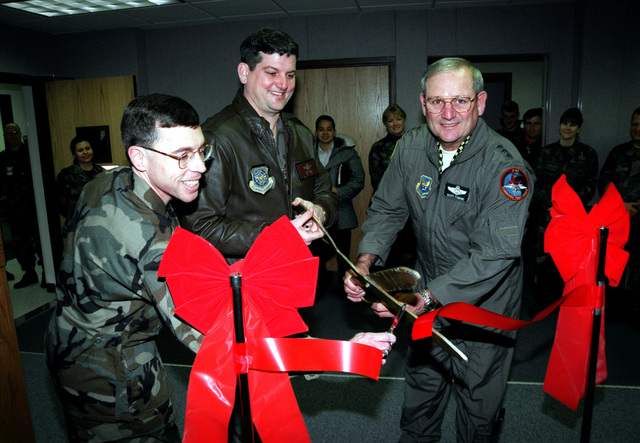 """Medium shot, front view, from the left, 319th Air Refueling Wing CHIEF of Command and Control Lieutenent Colonel Cliff Fitts, 319th Air Refueling Wing Commander Colonel V.M. """"Rusty"""" Findley, and Air Force Deputy CHIEF of STAFF for Air and Space Operations Lieutenent General Marvin R. Esmond cut the ribbon officially opening the newly renovated Command Post at Grand Forks Air Force Base, ND. The ceremony for the $1.14 million project took place on 26 January 2000"""