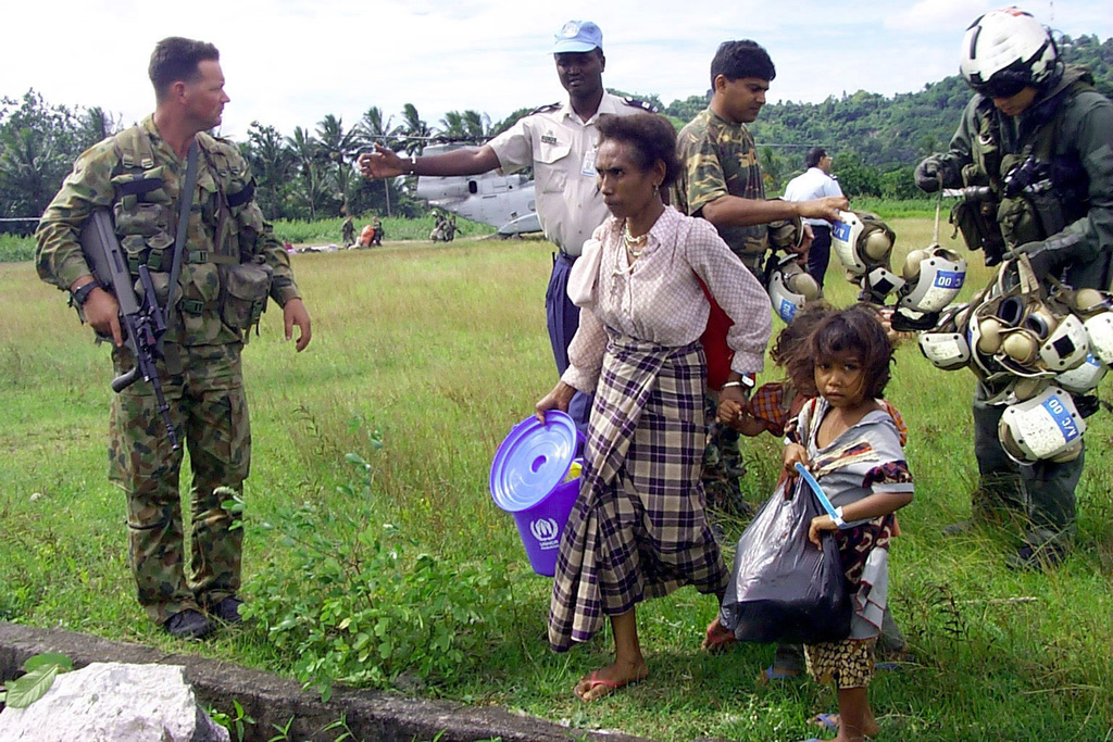 A displaced mother and her daughters come home to East Timor, months after fleeing the unrest there. Marine Medium Helicopter Squadron 265 brought three CH-46E Sea Knight helicopters to provide approximately 44 men, women and children with transportation home. A Marine collects the helicopter safety gear (right), while in the distance Marines unload the passenger's baggage from one of the CH-46Es. HMM-265 (minus) is the Air Combat Element of Special Purpose Marine Air Ground Task Force (SPMAGTF) East Timor. SPMAGTF East Timor is in the area aboard USS JUNEAU (LPD 10) and supports International Forces, East Timor's, turnover to the new United Nations Transitional Administration East Timor