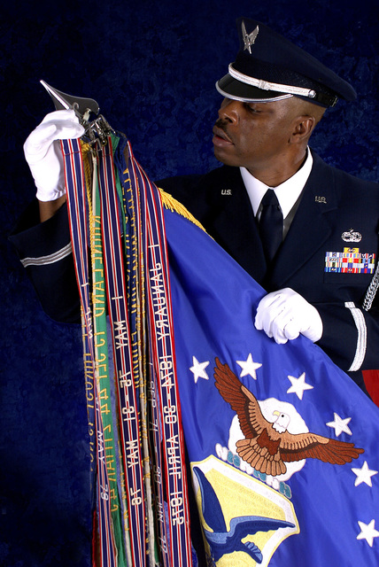 Medium close shot. MSGT Kenneth Moore, NCOIC 436th Honor Guard places the streamer for Dover AFB's Air Force Outstanding Unit Award in the 436th Airlift Wing guidon