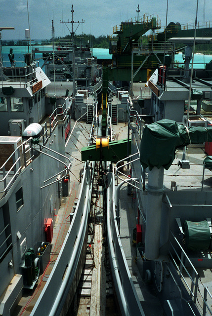 A vertical view of the deck cargo onboard the Military Sealift Command's (MSC) Afloat Prepositioning Force (APF) ship MV STRONG VIRGINIAN (T-AKR 9025) tied up at the pier. It includes the US Army's utility landing craft CEDAR RUN (LCU 2010), KENNESAW MOUNTAIN (LCU 2002), LCU 2008 and LCU 2003. The view is looking aft from the back of the wheelhouse