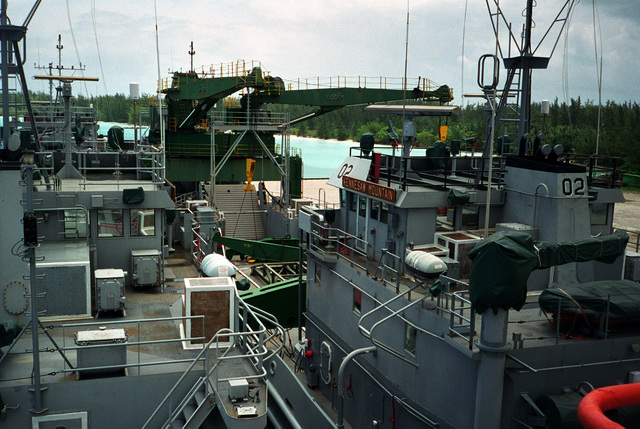A view of the deck cargo onboard the Military Sealift Command's (MSC) Afloat Prepositioning Force (APF) ship MV STRONG VIRGINIAN (T-AKR 9025) tied up at the pier. It includes the US Army's utility landing craft CEDAR RUN (LCU 2010), KENNESAW MOUNTAIN (LCU 2002), LCU 2008 and LCU 2003. The view is looking astern from the back of the wheelhouse