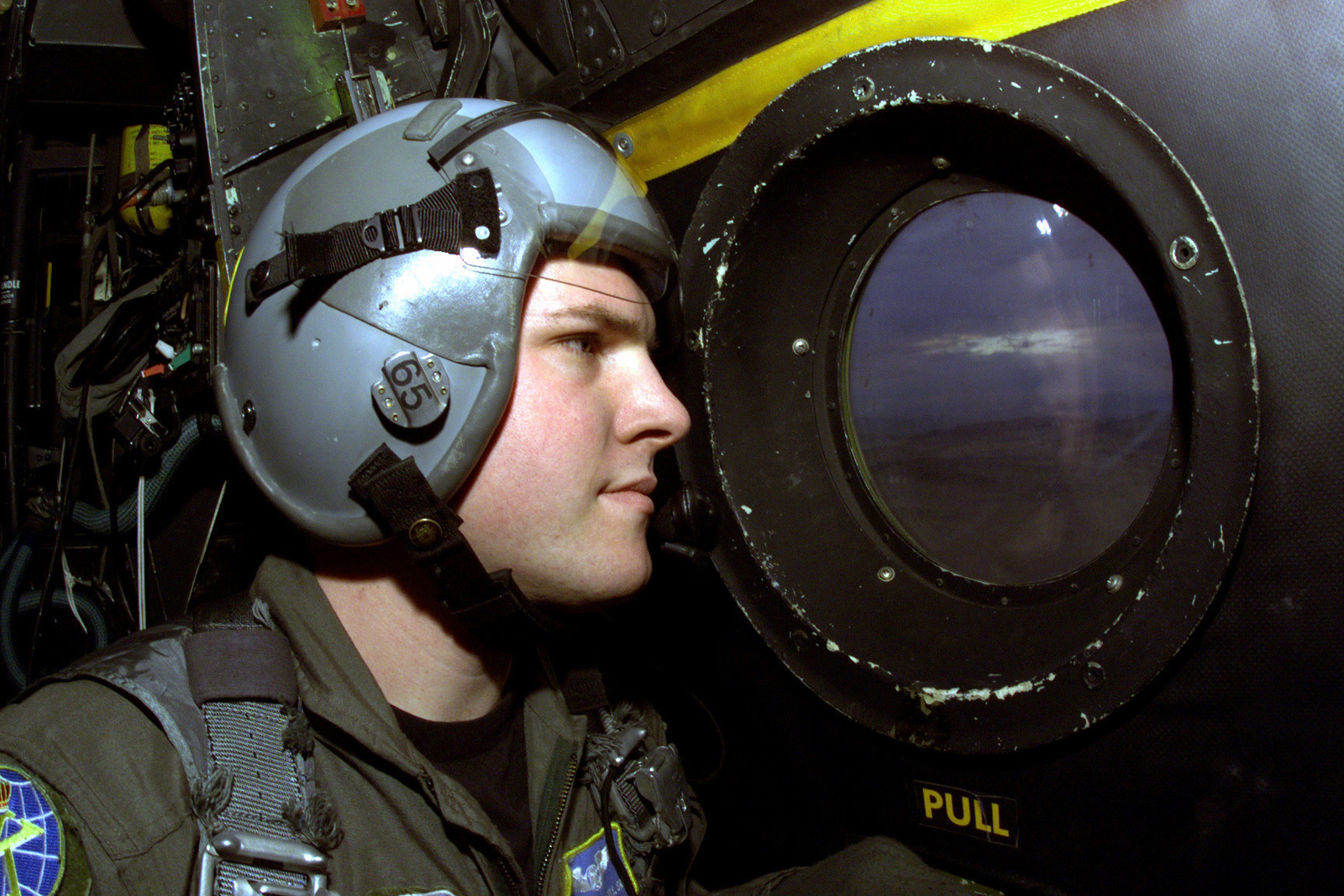 Interior, right side profile, close-up shot as USAF SENIOR AIRMAN Marshall W. Deny of the 9th Special Operation Squadron, looks out the troop door window of a HC-130 aircraft, prior to a static line high altitude low opening exercise over a drop zone near Naval Air Station, Fallon, Nevada. Members of the 9th Special Operation Squadron, are participating in a multi-service rescue exercise to prepare for themselves for when a real situation may occur