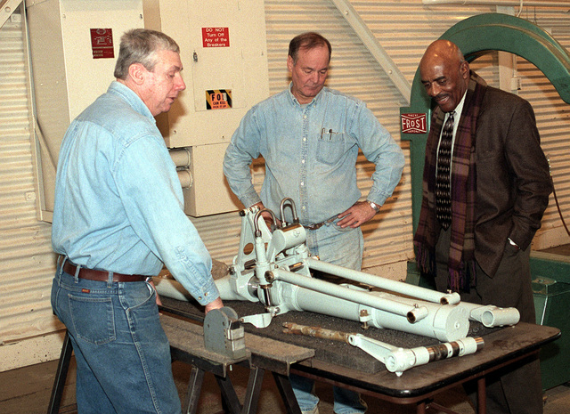 Medium shot, right front view, David McCloud Foundation members Don Delk (left), and Ed Lamm (center) show CHIEF MASTER Sergeant of the Air Force (Retired) Thomas M. Barnes P-38 wreckage, landing gear, which the McCloud members are restoring as part of Project Lighting Save