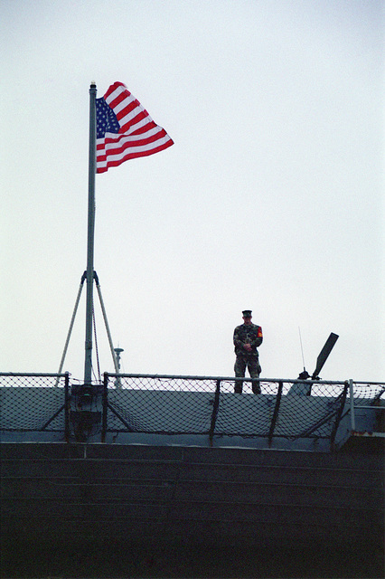 Onboard the USS FORT MCHENRY (LSD 43) Private First Class (PFC) Todd P. Willis, USMC, 1ST Battalion, 3rd Regiment, 3rd Marine Division, stands guard duty as the American Flag flies at full mast, while in port at Hong Kong, China. FORT MCHENRY is enroute to the Philippines to take part in Exercise BALIKATAN 2000