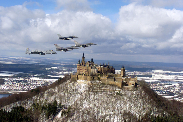 The US Air Force flagships of the 52d Fighter Wing, Spangdahlem Air Base, Germany, fly over Hohenzollern Castle (Burg Hohenzollern) in northern Germany. Spangdahlem Air Base consists of two F-16 squadrons, the 22nd and 23rd Fighter Squadrons, and the 81st Fighter Squadron, which flies the A-10 Thunderbolt II. Three F-16c Falcons lead the formation followed by the A-10