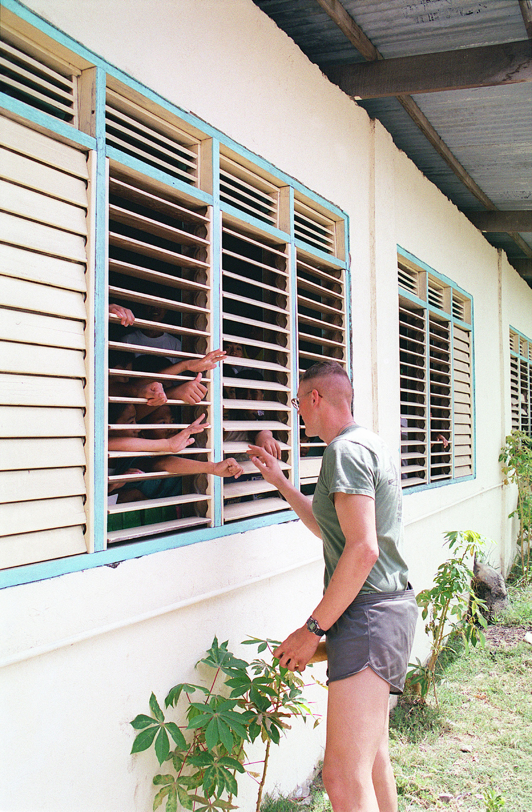 Lance Corporal (LCPL), Jonathan K. Huckstep, USMC, 1ST Battalion, 3rd Regiment, 3rd Marine Division, Okinawa, shakes hands with students through the shutter windows at Sapang Elementary School, Philippines. LCPL Huckstep is taking part in the community relations campaign during Exercise BALIKATAN 2000. BALIKATAN 2000 is a joint combined field training exercise held between US and Philippines forces, and is the largest of its kind since 1995