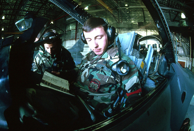 """A fish-eye lens view of US Air Force Avionics Maintenance Technicians AIRMAN First Class Richard Finger (right) and A1C Jared McCarthy as they perform a F-16 Falcon aircraft control check inside a Hangar at Hill AFB, Utah. From the March 2000 AIRMAN Magazine article """"No More Guessing Games."""""""