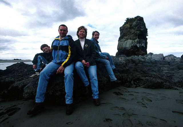 """US Air Force MASTER Sergeant Eric Davis his wife Lisa, daughter Jenny, and son Kevin sit on a rock formation along the beach at Christchurch, New Zealand where MSGT Davis is serving a three-year special duty assignment. From the March 2000 AIRMAN Magazine article, """"The 'Kiwi' Clan"""""""