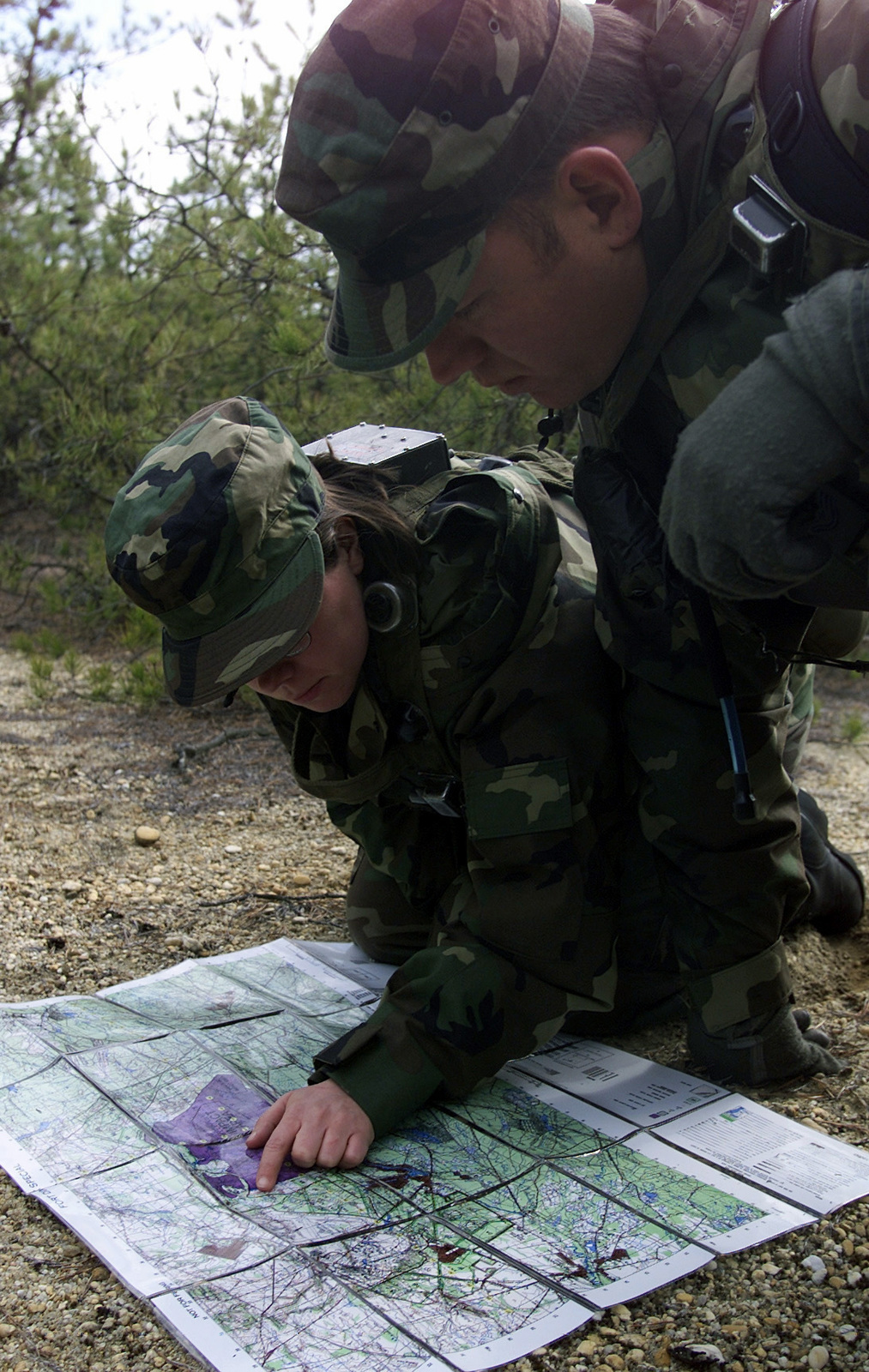Left side front view, medium close-up as US Air Force AIRMAN First Class Dawn Anderson (l), and Technical Sergeant Randy Lewis, find their grid coordinates on a map during the Land Navigation portion of the Phoenix Readiness Combat Course, Thursday, March 2,2000. A1C Anderson is assigned to the 1ST Combat Camera, Squadron, Charleston AFB, South Carolina and TSGT Lewis is assigned to the 367th Training Support Squadron, Hill AFB, Utah. Both are deployed to the Air Mobility Warfare Center, Fort Dix, New Jersey, for the Phoenix Readiness Combat Course