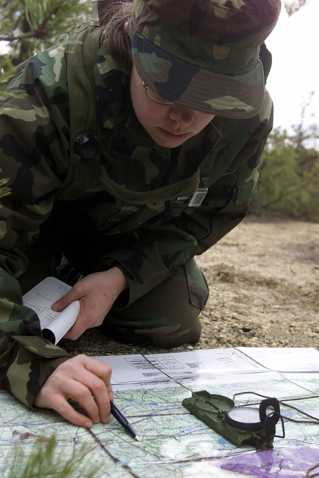 Straight on medium close-up shot as US Air Force AIRMAN First Class Dawn Anderson tries to find her grid coordinate on a map during the Land Navigation course, Thursday, March 2, 2000. A1C Anderson is assigned to the 1ST Combat Camera Squadron, Charleston AFB, South Carolina, and deployed to the Air Mobility Warfare Center, Fort Dix, New Jersey, for the Phoenix Readiness Combat Course