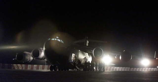"""Left side front view medium shot of as personnel (equipment and personnel not shown) from the 721st Air Mobility Squadron at McGuire Air Force Base, New Jersey, and maintainers from Dover Air Force Base, board a C-17A Globmaster III, bound for """"Operation Atlas Response."""" The C-17A Globemaster III aircraft, will take them to Hoedspruit AFB, South Africa, and will be the first of several flights that will arrive throughout the following weeks bringing helicopters and military personnel to assist with search and rescue and with the distribution of relief supplies in Mozambique"""