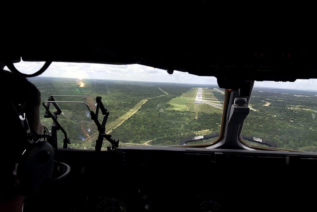"An interior shot over the right shoulder and out the front window as Major Ronald Whittle, a pilot assigned to the 17th Airlift Squadron at Charleston Air Force Base, South Carolina, guides the first C-17A Globemaster III, to a landing at Hoedspruit AFB, South Africa, after traveling from the United States to take part in ""Operation Atlas Response."" The C-17A is the first of several flights that will arrive throughout the following weeks bringing helicopters and military personnel (equipment and personnel not shown) to assist with search and rescue and with the distribution of relief supplies in Mozambique"