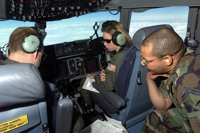 """Interior cockpit shot as SENIOR MASTER Sergeant Libby Quinlan, an air transportation manager assigned to the 721st Air Mobility Squadron at McGuire Air Force Base, New Jersey, and Lieutenant's James Beyer and Erin Markwith, pilots assigned to the 17th Airlift Squadron at Charleston Air Force Base, South Carolina, radio ahead for information at the destination of their C-17A Globemaster III, which is bound for Hoedspruit AFB, South Africa, to take part in """"Operation Atlas Response."""" The C-17A is the first of several flights that will arrive throughout the following weeks bringing helicopters and military personnel (equipment and personnel not shown) to assist with search and rescue and ..."""