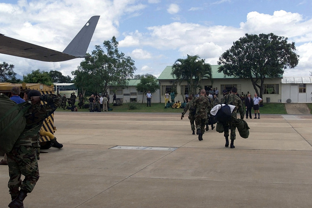 """Rear view long shot as Personnel (equipment and personnel not shown) from the 721st Air Mobility Squadron at McGuire Air Force Base, New Jersey, and maintainers from Dover Air Force Base, arrive at Hoedspruit AFB, South Africa, to take part in """"Operation Atlas Response."""" They are the first of several flights that will arrive throughout the following weeks bringing helicopters and military personnel to assist with search and rescue and with the distribution of relief supplies in Mozambique"""