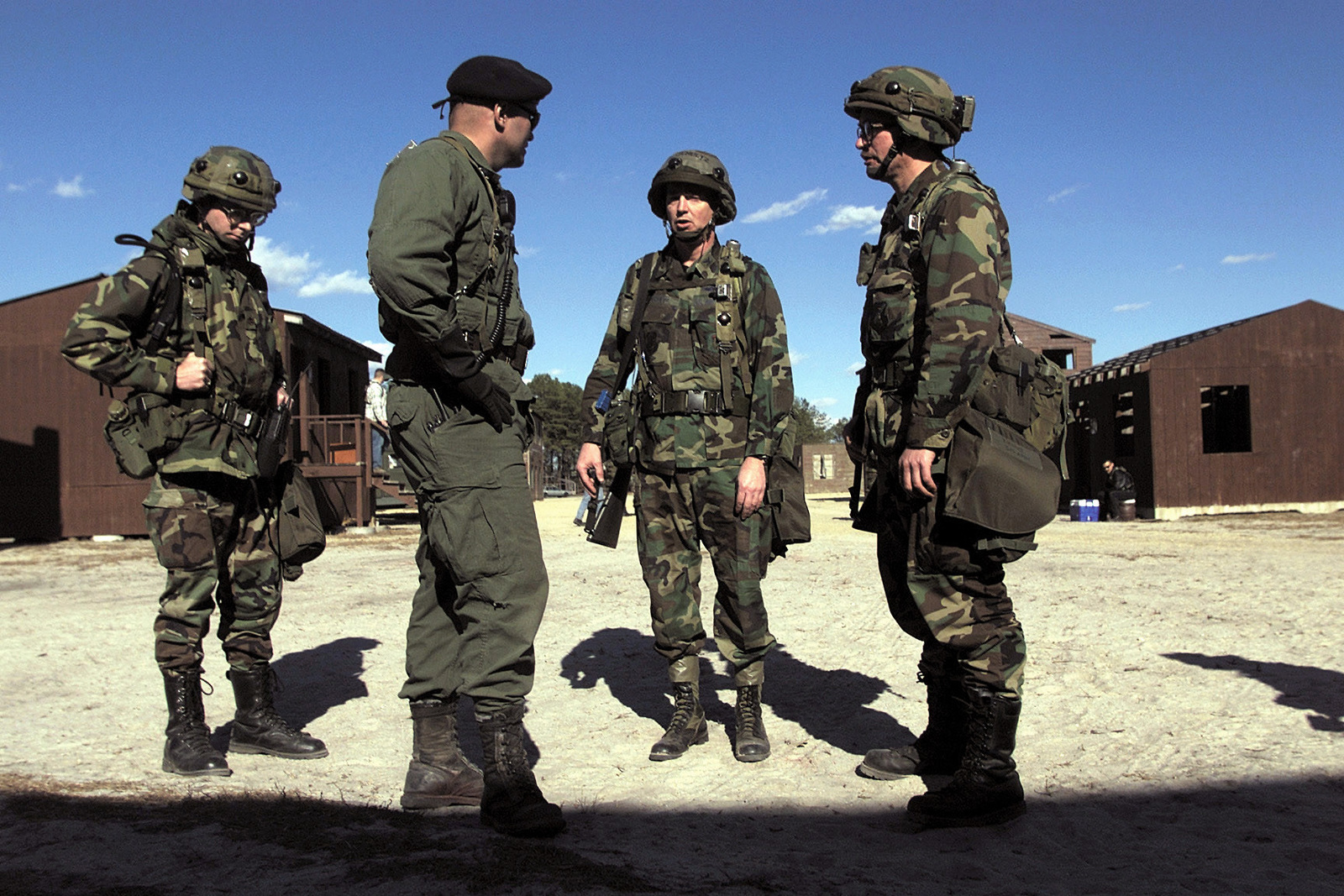 Straight on medium shot as US Air Force Colonel Mark Schultz (2nd from right), and Lieutenant Colonel Steve Kinne(far right), talk to the host nation security forces chief about the local criminal element, during field training exercises, Sunday, March 5, 2000. COL Schultz is the Operations Group Commander with 319th Air Refueling Wing, Grand Forks, North Dakota and LTC Kinne is assigned to 319th Medical Squadron, Grand Forks, North Dakota. Both are deployed to the Air Mobility Warfare Center, Fort Dix, New Jersey for the Phoenix Readiness Combat Course