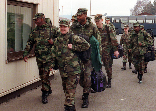 "Medium shot, front view, personnel, carrying individual luggage, 86th Airlift Wing, Ramstein Air Base, Germany, walk toward camera, prepare for departure on 7 March 2000, for Operation ""BRILLIANT LION,"" in Cameroon, Africa. ""BRILLIANT LION"" is a medical exercise to provide medical aide to six villages in Cameroon and is the largest medical exercise of its type for the United States European Command"