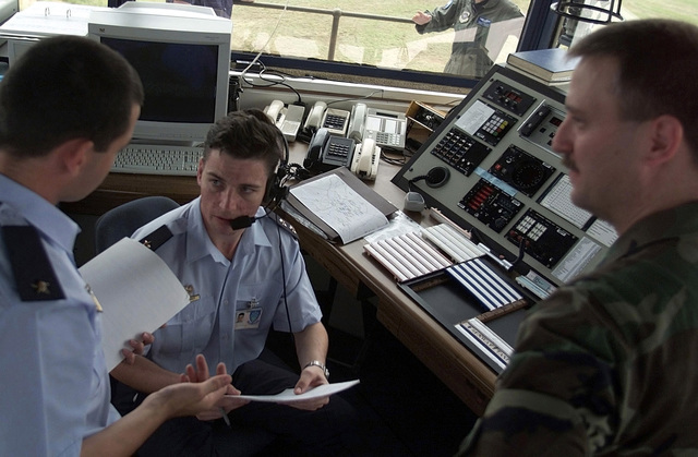 Left side profile medium close-up as Captain Chris Wheeler, assigned to the 52nd Fighter Wing at Spangdalem Air Base, Germany, and working as an Air Traffic Control Liason at Hoedspruit Air Force Base in South Africa, works side-by-side with Leuitenant Fairhurst, a South African Air Force Air Traffic Controller, to coordinate aircraft (not shown) departure clearances for U.S. Air Force aircraft deployed to Hoedspruit Air Force Base, during Operation Atlas Response. The U.S. aircraft are deployed to South Africa to provide humanitarian relief to the people forced from their homes in the flooded regions of Mozambique