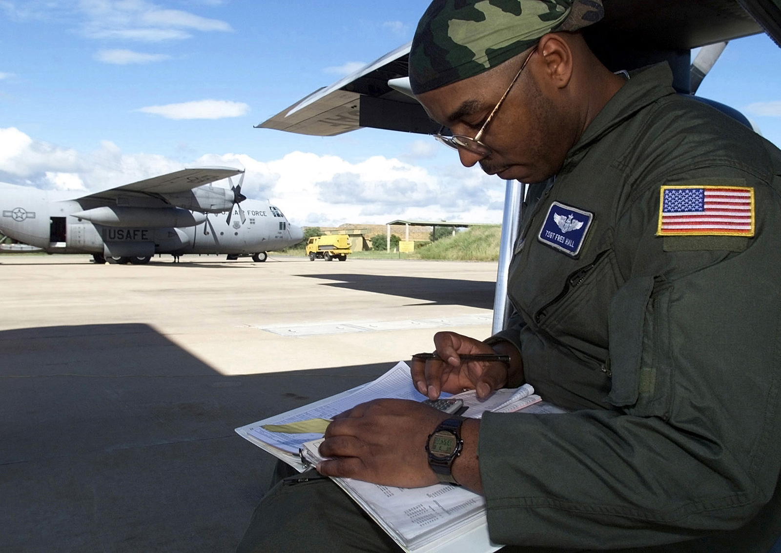 Left side profile medium close-up shot as USAF Technical Sergeant Fred Hall, a C-130 loadmaster from the 37th Airlift Squadron, 86th Airlift Wing, Ramstein Air Base, Germany, checks aircraft weight and balance prior to departing Hoedspruit Air Force Base, South Africa, to deliver U.S. personnel (cargo and personnel not shown) and supplies to Beira, Mozambique, during Operation Atlas Response. The U.S. aircraft are deployed to South Africa to provide humanitarian relief to the people (not shown) forced from their homes in the flooded regions of Mozambique. A right side profile of a USAF C-130 Hercules cargo aircraft is seen in the background