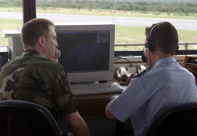 Rear view medium shot over the right shoulder as Captain Chris Wheeler, assigned to the 52nd Fighter Wing at Spangdalem Air Base, Germany, and working as an Air Traffic Control Liason at Hoedspruit Air Force Base in South Africa, works side-by-side with Lieutenant Fairhurst, a South African Air Force Air Traffic Controller, to coordinate aircraft departure clearances for U.S. Air Force aircraft (not shown) deployed to Hoedspruit Air Force Base, during Operation Atlas Response. The U.S. aircraft are deployed to South Africa to provide humanitarian relief to the people (not shown) forced from their homes in the flooded regions of Mozambique