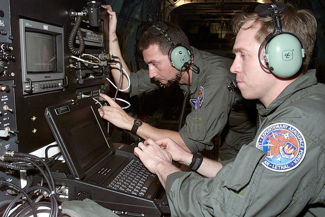 Left side profile medium close-up shot of US Air Force STAFF Sergeants Rob Turner (Foreground) and Todd Geehan (Background), assigned to the 32nd Air Operations Group at Ramstein Air Base, Germany, prepare a Keen Sage aerial surveillance system, operated from a specially prepared C-130, for a flight over Southern Mozambique to search for stranded flood victims and to survey water levels and damage caused by the recent flooding (Not shown) in Southern Africa. The 37th Airlift Squadron C-130 aircraft, are deployed from Ramstein Air Base, Germany, to Hoedspruit Air Force Base, South Africa, as part of the United States Operation Atlas Response, humanitarian relief efforts and to fly daily, ...