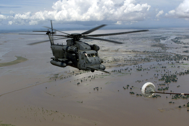 "Right side front view medium long aerial shot as a US Air Force MH-53M ""Pave Low IV"" helicopter assigned to the 21st Special Operations Squadron, Royal Air Force, Mildenhall (Only the refueling hose and drag chute from the MC-130P is seen), flies over flooded Central Mozambique near the town of Chibuto as it refuels from an MC-130P ""Shadow"" from the 67th Special Operations Squadron, Royal Air Force Mildenhall. The MH-53M Pave Lows are operating from Air Force Base Hoedspruit in South Africa, where they are deployed in support of Operation Atlas Response. Operation Atlas Response is a multi-national humanitarian relief mission helping displaced people (Not shown) in Central and Southern ..."