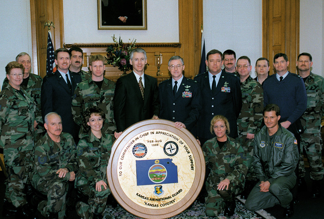 16 members of the 190th Air Refueling Wing, Kansas Air National Guard, present Kansas Governor Bill Graves a plaque on March 23, 2000 for his support of the unit's 1999 missions. The Topeka, Kansas based KC-135 unit deployed twice to Incirlik Air Base, Turkey in support of Operation Northern Watch and also served the first few weeks of Operation Allied Force. Governor Graves (center) accepted the plaque from 190th ARW Commander, Colonel Rufus L. Forrest, Jr. (standing left of Gov Graves) during a ceremony at the Kansas statehouse. The metal and wooden plaque was designed and built by Turkish artisans and highlighted by 190th ARW member STAFF Sergeant Gary Filkens, unit artist and member ...