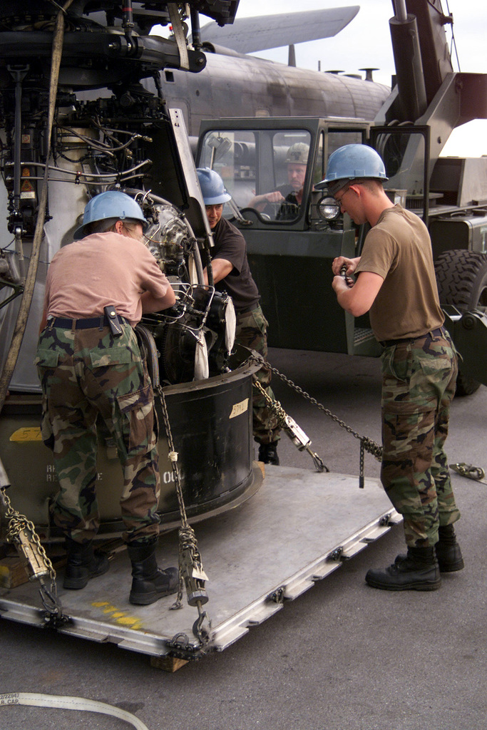 Medium shot. Maintainers from the 352nd Maintenance Squadron, Royal Air Force, Mildenhall, move the gear box of an MH-53M Pave Low IV helicopter to its transpot box so it will fit on a C-5 for re-deployment from Air Force Base Hoedspruit, South Africa. The 352nd is deployed here in support of Operation Atlas Response, a humanitarian relief mission in southern Africa
