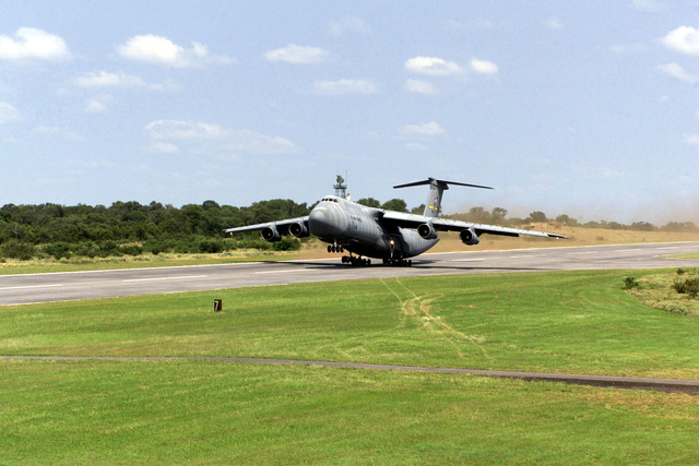 Extreme long shot. A heavily laden C-5 Galaxy begins to lift as it departs for Royal Air Force Base Mildenhall, United Kingdom, as they assist in the re-deployment from Air Force Base Hoedspruit, South Africa. U.S. Forces were deployed to southern Africa as part of Operation Atlas Response, a humantiarian relief mission in South Africa and Mozambique