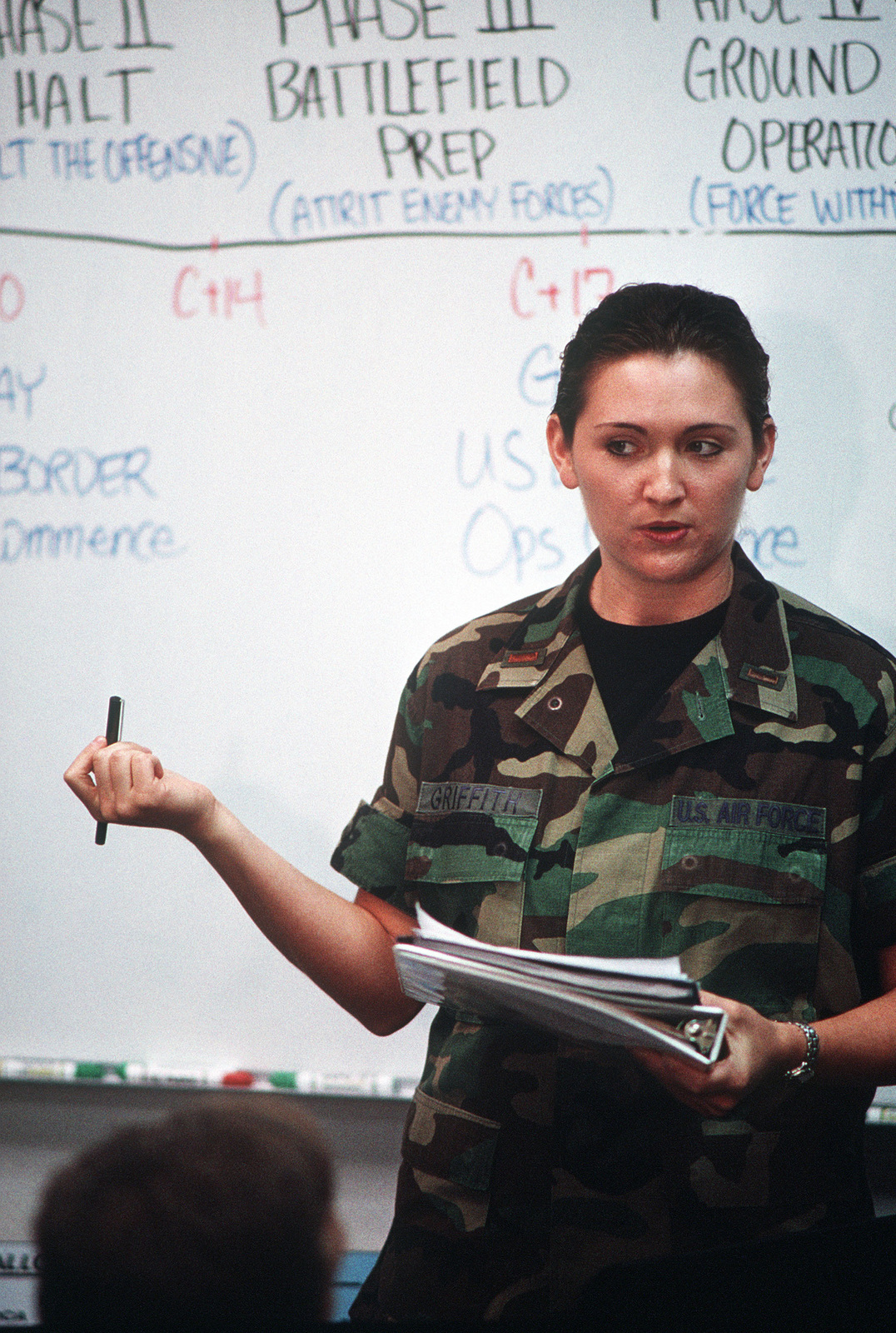 """During a briefing in the simulated Joint Air Operations Center, Hill Air Force Base, Utah, US Air Force 2nd Lieutenant Robyn Griffith talks to members of her class about intelligence gathered by Air Force Space Command. This image was used in the April 2000 AIRMAN Magazine article """"Airmanship 101."""""""