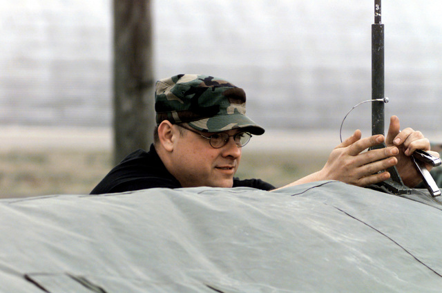 A US Air Force ADVON (Advanced Echelon) team member, SENIOR AIRMAN Ryon Ajello, of the 89th Civil Engineering Squadron, Andrews Air Force Base, Maryland, secures the rain cover support post on Survivor Recovery Center tent at Fort A.P Hill, Virgina, during Exercise Crisis Look 00-03