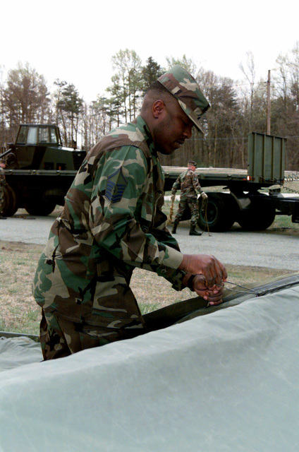 US Air Force MASTER Sergeant Vincent Cephous of the 89th Air Wing, Civil Engineering Squadron, Andrew AIr Force Base, Maryland, is lacing the tent skin of the Survivor Recovery Center at Fort A.P. Hill, Virgina, during Exercise Crisis Look 00-03