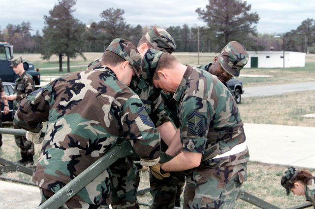 US Air Force members of the 89th Air Wing ADVON (Advanced Echelon) team join together to support the frame of a Temper tent while trying to correctly position a suspension pin during Exercise Crisis Look 00-03 at Fort A.P. Hill, Virginia