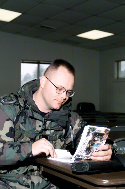 US Air Force STAFF Sergeant Russell Ware, of the 89th Air Wing, Security Forces Squadron, reviews information in the Air Force AIRMAN's Manual as he waits for the arrival of other 89th SFS members to arrive at Fort A.P. Hill, Virginia, to participate in Exercise Crisis Look 00-03