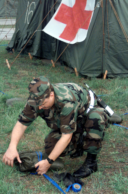US Air Force Major John Beery, psychologist for the 89th Medical Operations Squadron, Andrews Air Force Base, Maryland, lays simulated sandbags around a medical tent at a deployed site at Fort A.P. Hill, Virginia. During the deployment to Exercise Crisis Look 00-03, wing personnel will be evaluated on Ability to Survive and Operate (ATSO) skills, humanitarian scenarios and base defense. The primary objectives of this exercise are to train and prepare troops for Aerospace Expeditionary Force deployments