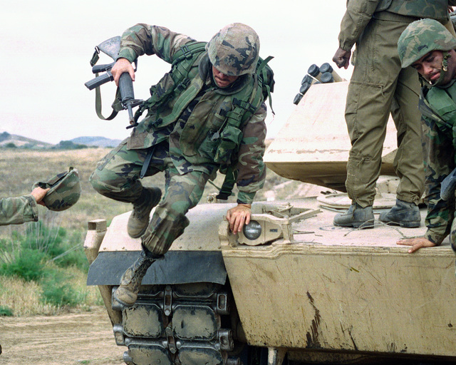 US Marine Corps Corporal (CPL) Eric J. Staley, 2nd Battalion 7th Marine Regiment, holding a 5.56mm M16A2 assault rifle jumps off an M1A1 Abrams Main Battle Tank (MBT) during an Amphibious Operation Training (AOT) Exercise at Camp Pendleton, California