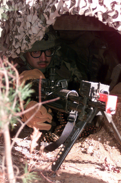 Medium close, up front view, SENIOR AIRMAN Jaime Velazquez, USAF, 89th Air Wing Security Forces Squadron, Andrews Air Force Base, Maryland, under camouflage netting, manning a bipod mounted M60 machine gun equipped with Multiple Integrated Laser Engagement System (MILES). He is manning his Defensive Fighting Position at Fort A. P. Hill during exercise Crisis Look 00-03