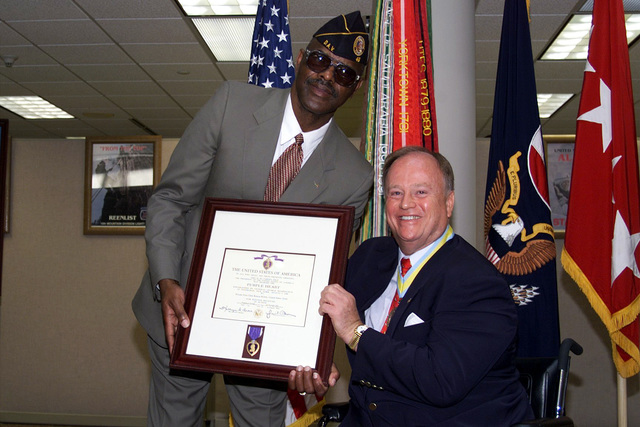 Senator Max Clelland (D-GA) presents the Purple Heart to US Army Sergeant First Class (retired) Roscoe Killett, for wounds he received as a Private First Class on November 29, 1965, while serving in Vietnam with weapons platoon, B Company, 173rd Airborne Brigade