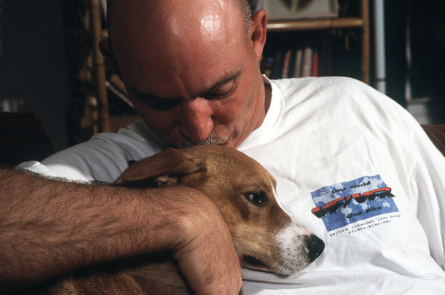 "A close up view of US Air Force SENIOR MASTER Sergeant McCathern kissing one of his dogs. The dogs ""Buddie and Donut"" helped SMSGT McCathern to overcome severe depression, and his story is featured in the May 2000 AIRMAN Magazine article ""Returned to Duty."""