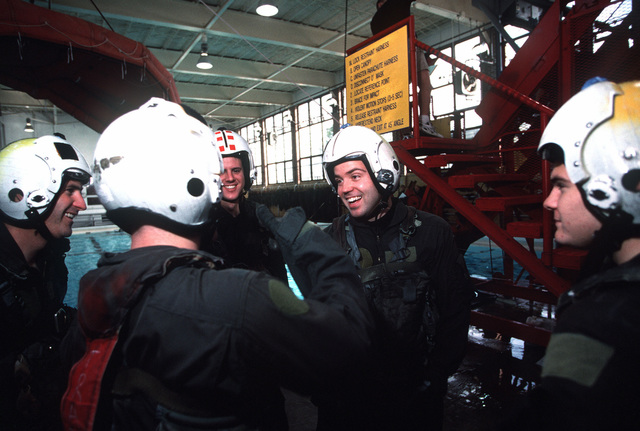 """US Navy ENSIGN Tom Kuruc, smiles after he and other students completed the first of two """"dunkers"""". Once the trainee is strapped into the """"dunker,"""" the cage slams into the water, rolls down the track and holds the student upside down. If the student moves too soon, the roll is nixed, and the student has to try again. This image was used in the May 2000 AIRMAN Magazine article """"Earning Wings of Silver & Gold"""""""